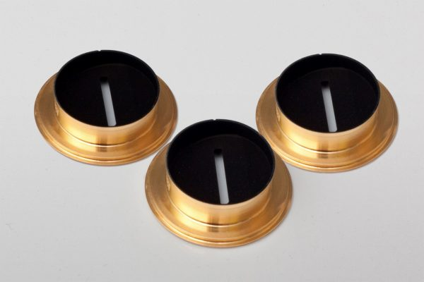3 metallic circular components coated with acktar's magic black coating